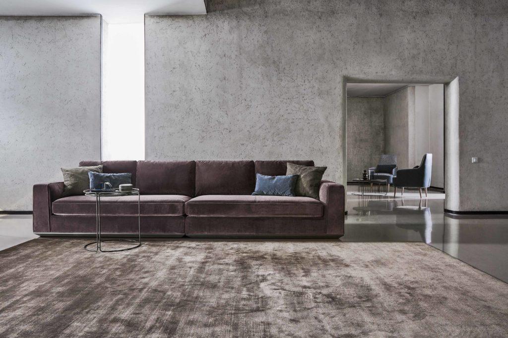 sofa velluto con tappeto in tinta e coppia poltroncine sullo sfondo
