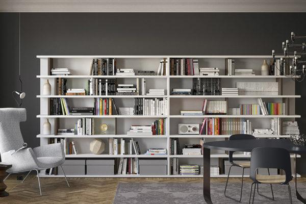 soggiorno con libreria a tutta parete e lampadario